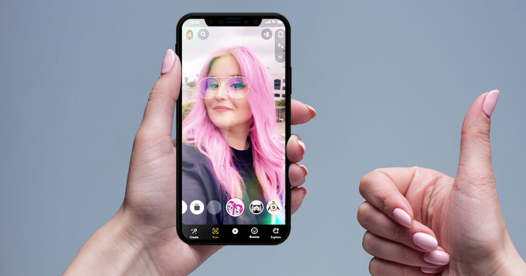 Woman using snapchat augmented reality lens that gives her pink her and pink glasses.